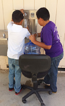Kids filling up at water bottle filling station.
