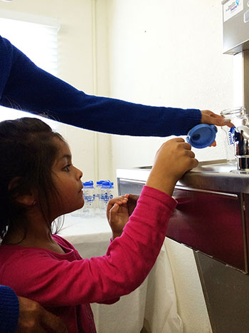 Little girl filling up her Agua4All water bottle.