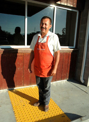 Chepo standing in front of his store.