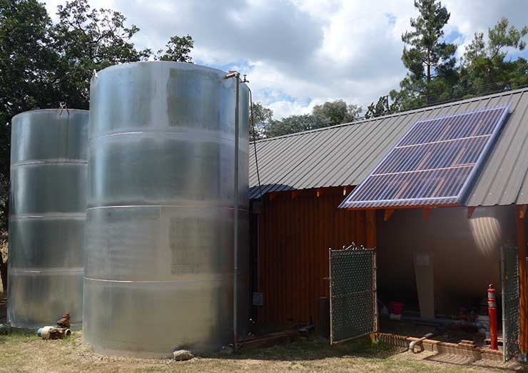Hydropneumatic tank inside well house with two water storage tanks outside.