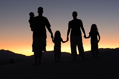Family of five silhouette walking into the sunset.
