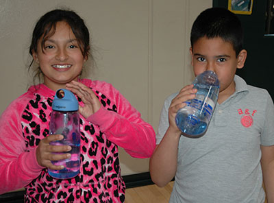 Elementary students drinking form water bottle