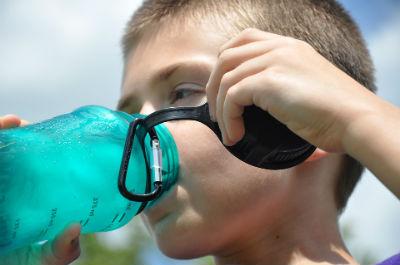 boy drinking water from waterbottle