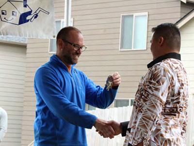 Housing Kitsap staff hands key to homeowner.
