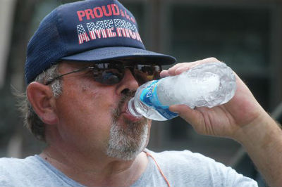 "Man drinks from water bottle, wearing ""Proud to be American"" hat."