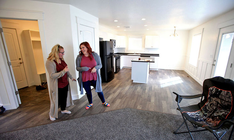 Loryn Law, right, laughs with Mikell Brown during a tour of her new home.