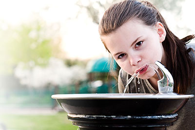 Girl drinking from drinking fountain