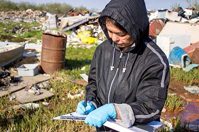 Jacqueline Shirley records data during landfill assessment.