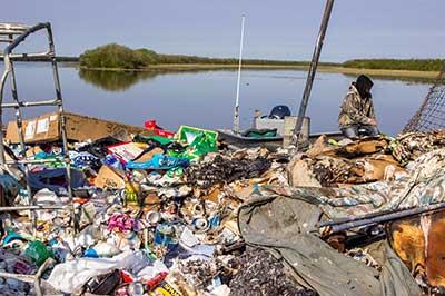 Victor Tunuchuk, Kotlik's Environmental Coordinator sitting in his boat aside the landfill.