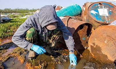 Victor Tunuchuk grabbing water sample from pre-determined site.