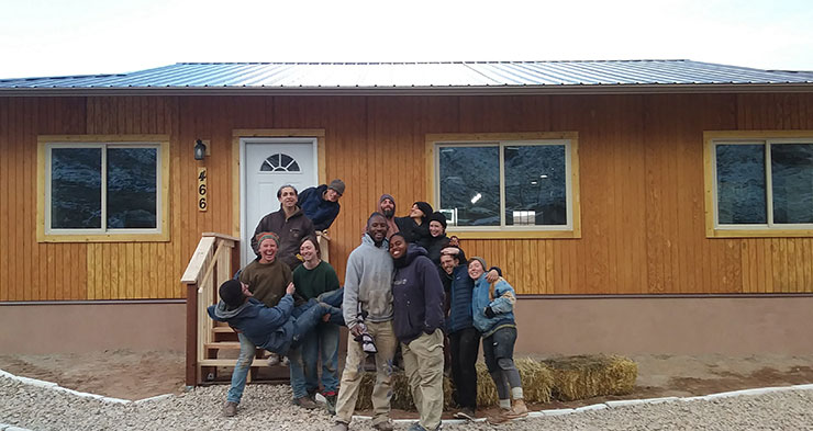Build participants standing in front of a nearly completed home.