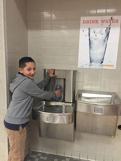 school child filling up water bottle